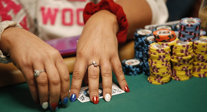 In this June 27, 2015, photo, Tanya Stendzis holds her cards while playing in the Ladies No-Limit Hold'em Championship during the World Series of Poker in Las Vegas. Poker is still a man's game if the numbers from the World Series of Poker are any clue. Just 4 percent of the 6,683 people who competed in 2014's Main Event were women and this year of the 22,374 entries in the Colossus, just 6 percent were women. Naturally, though, it's all ladies at the ladies-only event. (AP Photo/John Locher)