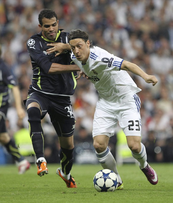 epa02671505 Real Madrid's German midfielder Mesut Oezil (R) vies for the ball with Tottenham's Brazilian midfielder Sandro Ranieri (L) during their UEFA Champions League quarterfinals match at Santiago Bernabeu stadium in downtown Madrid, Spain, 05 April 2011.  EPA/ALBERTO MARTIN