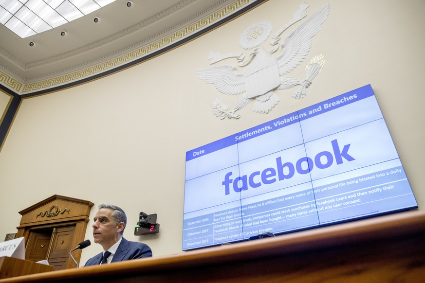 A list of settlements, violations and breaches scrolls over Facebook's logo on a screen behind David Marcus, CEO of Facebook's Calibra digital wallet service, left, as he speaks during a House Financial Services Committee hearing on Facebook's proposed cryptocurrency on Capitol Hill in Washington, Wednesday, July 17, 2019. (AP Photo/Andrew Harnik) David Marcus