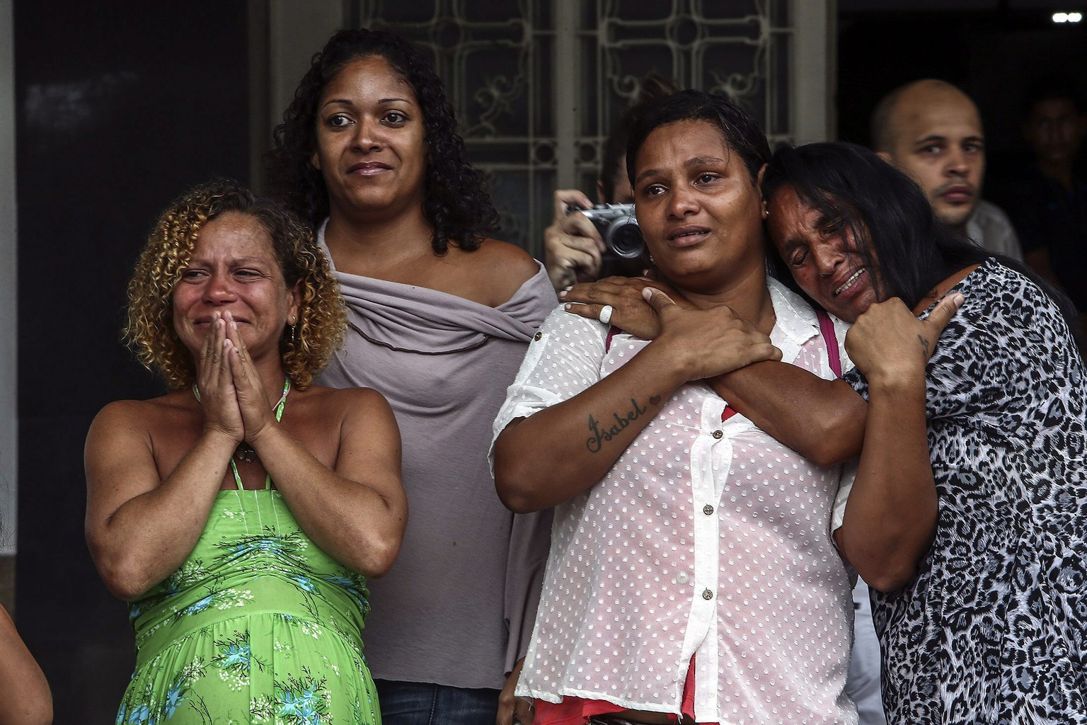 epa04179010 Women cry during the funeral of 25 year old dancer Douglas Pereira, who was a member of the dancing group from a popular television show and who died on 21 April lduring a police operation in the Pavao-Pavaozinho slum, in Rio de Janeiro, Brazil, 24 April 2014. The death of a dancer in one of Rio de Janeiro's slums touched off violent protests and sparked an investigation on 24 April into the role that the militarized police might have played. Eight officers with the so-called militarized police appeared on 24 April before the civilian police in the case, which was causing great tension in the city only 49 days ahead of the World Cup.  EPA/Antonio Lacerda