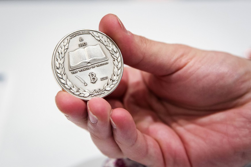 A man holds a Silver coin etched with the cryptographic information for digital Bitcoins in it during the