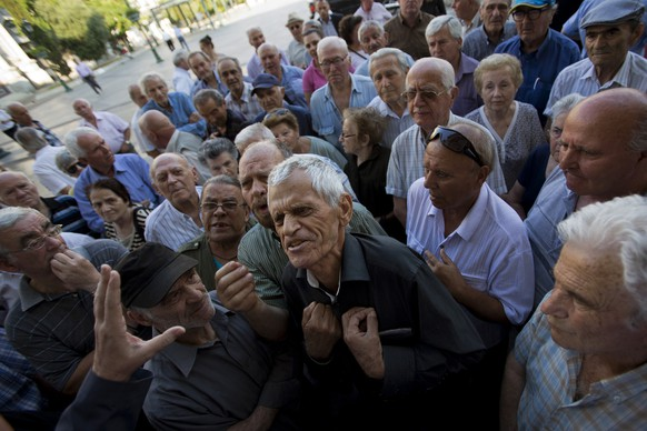 """Elderly people argue with a bank worker as they wait to be allowed into a bank to withdraw a maximum of 120 euros ($134) for the week in Athens, Monday, July 6, 2015. Greece's Finance Minister Yanis Varoufakis has resigned following Sunday's referendum in which the majority of voters said """"no"""" to more austerity measures in exchange for another financial bailout. (AP Photo/Emilio Morenatti)"""