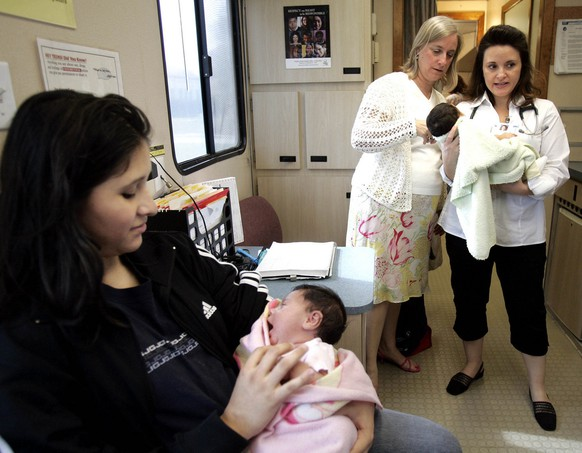 Evelyn Flores, 16, left, holds her one-month-old daughter Hailey Interiano as Dr. Angela Sanchez, right, and social worker Kathy Bennett check on one-month-old Cielo Angela Carrizalez at the mobile health clinic in Garland, Texas, in this April 11, 2006, photo.The clinic is just one way of helping teen mothers in Texas, which has the fifth-highest teen pregnancy rate in the nation, according to David Landry of the Guttmacher Institute, a non-profit group that researches reproductive health. (AP Photo/LM Otero)