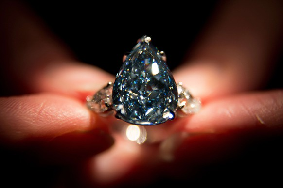 """(FILES) This photo taken on April 29, 2014, shows a Christie's auction house employee holding """"The Blue"""", the largest flawless vivid blue diamond in the world, during a photocall at the auction house in London. The world's largest blue diamond known as """"The Blue"""" was sold at a Christie's auction for 23,895 million dollars in Geneva on May 14, 2014. AFP PHOTO / LEON NEAL"""