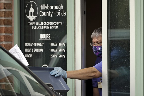 Hillsborough County Library Service employee Stephen Duran wears a mask and gloves to protect himself from the coronavirus outbreak as he hands out unemployment paperwork to residents Tuesday, April 14, 2020, at the Jimmie B. Keel Regional Public Library in Tampa, Fla. Florida's unemployment rate shot up to 4.3% in March, as coronavirus-induced closures of Florida's theme parks, hotels and large numbers of businesses caused the highest levels of joblessness in almost two years.  (AP Photo/Chris O'Meara) Stephen Duran