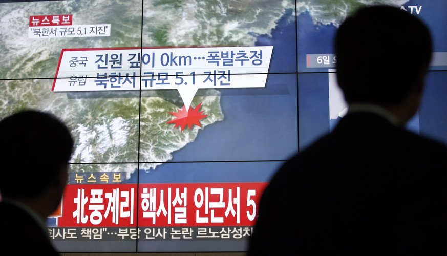 People walk by a screen showing the news reporting about an earthquake near North Korea's nuclear facility, in Seoul, South Korea, Wednesday, Jan. 6, 2016. South Korean officials detected an