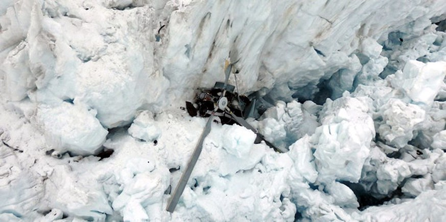 epa05035283 A handout photo provided by New Zealand Police shows a helicopter which crashed at Fox Glacier, New Zealand, 21 November 2015, killing all seven people aboard. A rescue team had reportedly been lowered from the air to the crash site and found no survivors. Officials said inclement weather and poor flying conditions would hamper recovery efforts for the remains.  EPA/NEW ZEALAND POLICE / HANDOUT BEST QUALITY AVAILABLE HANDOUT EDITORIAL USE ONLY/NO SALES
