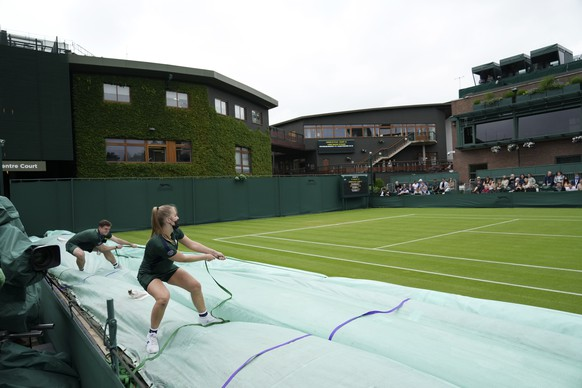 The rain covers are removed from the courts after a rain delay on day one of the Wimbledon Tennis Championships in London, Monday June 28, 2021. (AP Photo/Alberto Pezzali)
