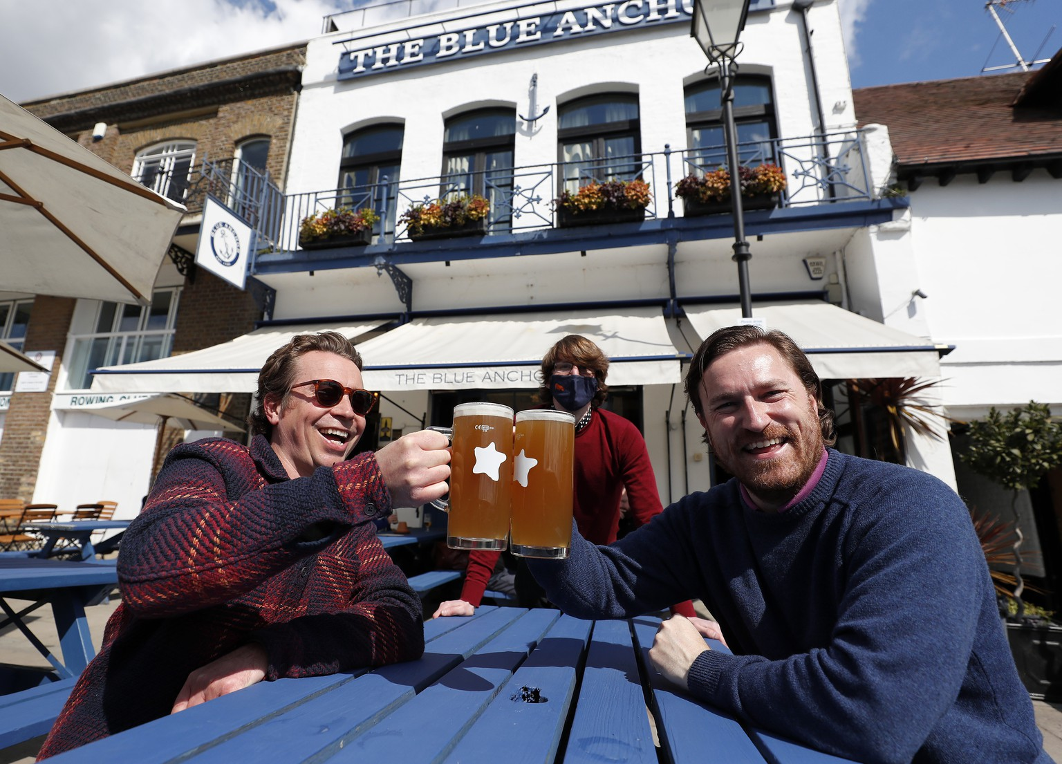 Matt and Matt enjoy their first beer outside the Blue Anchor pub on the embankment in Hammersmith, London, Monday, April 12, 2021. Millions of people in England will get their first chance in months for haircuts, casual shopping and restaurant meals on Monday, as the government takes the next step on its lockdown-lifting road map.(AP Photo/Frank Augstein)