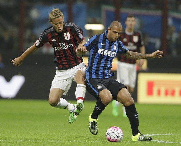 AC Milan's Keisuke Honda, left, challenges for the ball with Inter Milan's Felipe Melo during a Serie A soccer match between Inter Milan and AC Milan, at the San Siro stadium in Milan, Italy, Sunday, Sept. 13, 2015. (AP Photo/Luca Bruno)