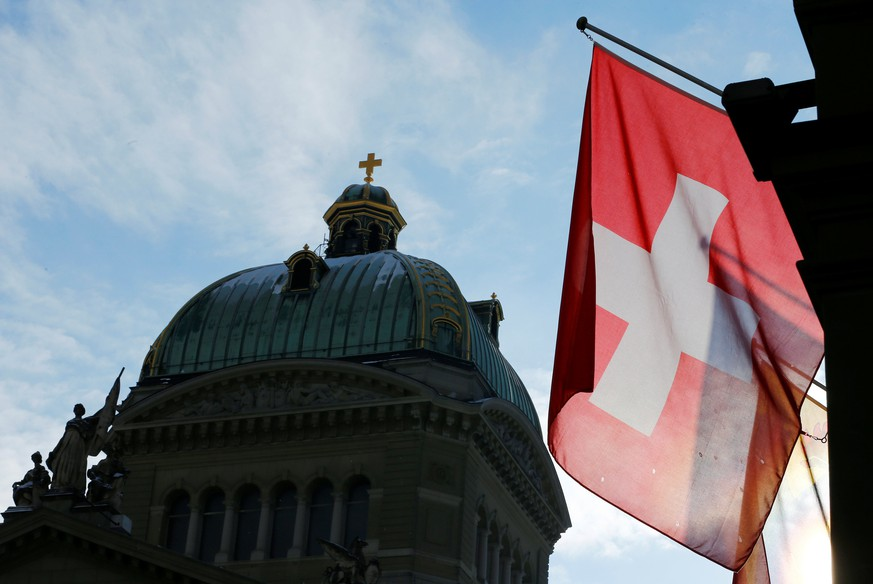 A Swiss flag is pictured in front of the Federal Palace (Bundeshaus) is pictured in Bern, Switzerland, January 16, 2017. Picture taken on January 16, 2017. REUTERS/Denis Balibouse