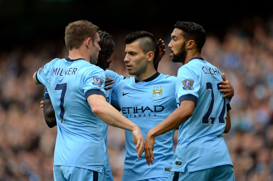 MANCHESTER, ENGLAND - OCTOBER 18:  Sergio Aguero (C) of Manchester City is congratulated by teammates after scoring the opening goal during the Barclays Premier League match between Manchester City and Tottenham Hotspur at Etihad Stadium on October 18, 2014 in Manchester, England.  (Photo by Michael Regan/Getty Images)