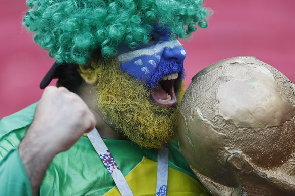 Brazil's supporter poses with a model of the World Cup trophy as he waits for the start of the quarterfinal match between Brazil and Belgium at the 2018 soccer World Cup in the Kazan Arena, in Kazan, Russia, Friday, July 6, 2018. (AP Photo/Frank Augstein)