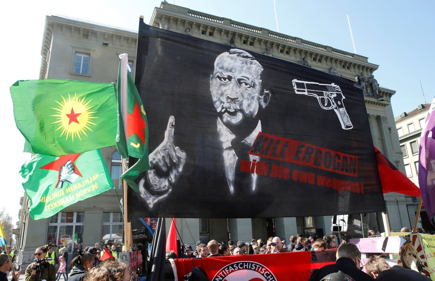 FILE PHOTO: People hold banners and flags during a demonstration against Erdogan dictatorship and in favour of democracy in Turkey, in Bern, Switzerland March 25, 2017. REUTERS/Ruben Sprich/File Photo