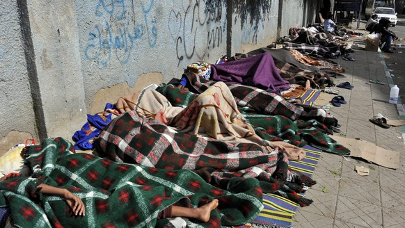 epa04190193 Eritrean refugees sleep on the sidewalk of a street as they wait for help from UNHCR in Sana'a, Yemen, 03 May 2014. Reports state over 210 Eritrean refugees, including women and children, called on the UN Refugee Agency to provide them with protection and assistance, especially most of them allegedly having fled from Eritrea to Yemen to avoid forced military service. EPA / YAHYA ARHAB