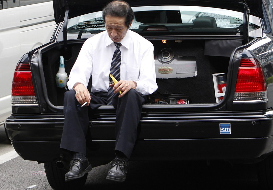 A taxi driver takes a rest, sitting on a car trunk in Tokyo, Japan, Tuesday, May 17, 2011. (AP Photo/Shizuo Kambayashi)