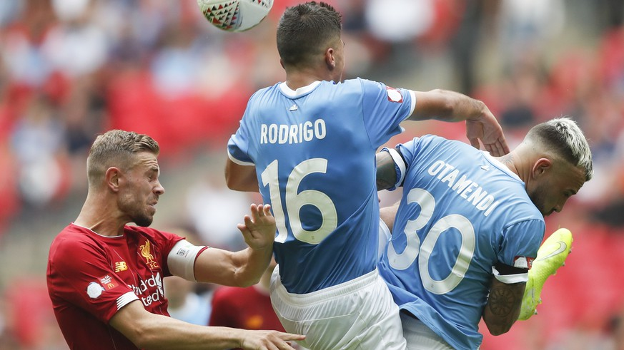 Liverpool's Jordan Henderson, left, vies for the ball with Manchester City's Rodrigo, centre, and Manchester City's Nicolas Otamendi during the Community Shield soccer match between Manchester City and Liverpool at Wembley Stadium in London, Sunday, Aug. 4, 2019. (AP Photo/Frank Augstein)