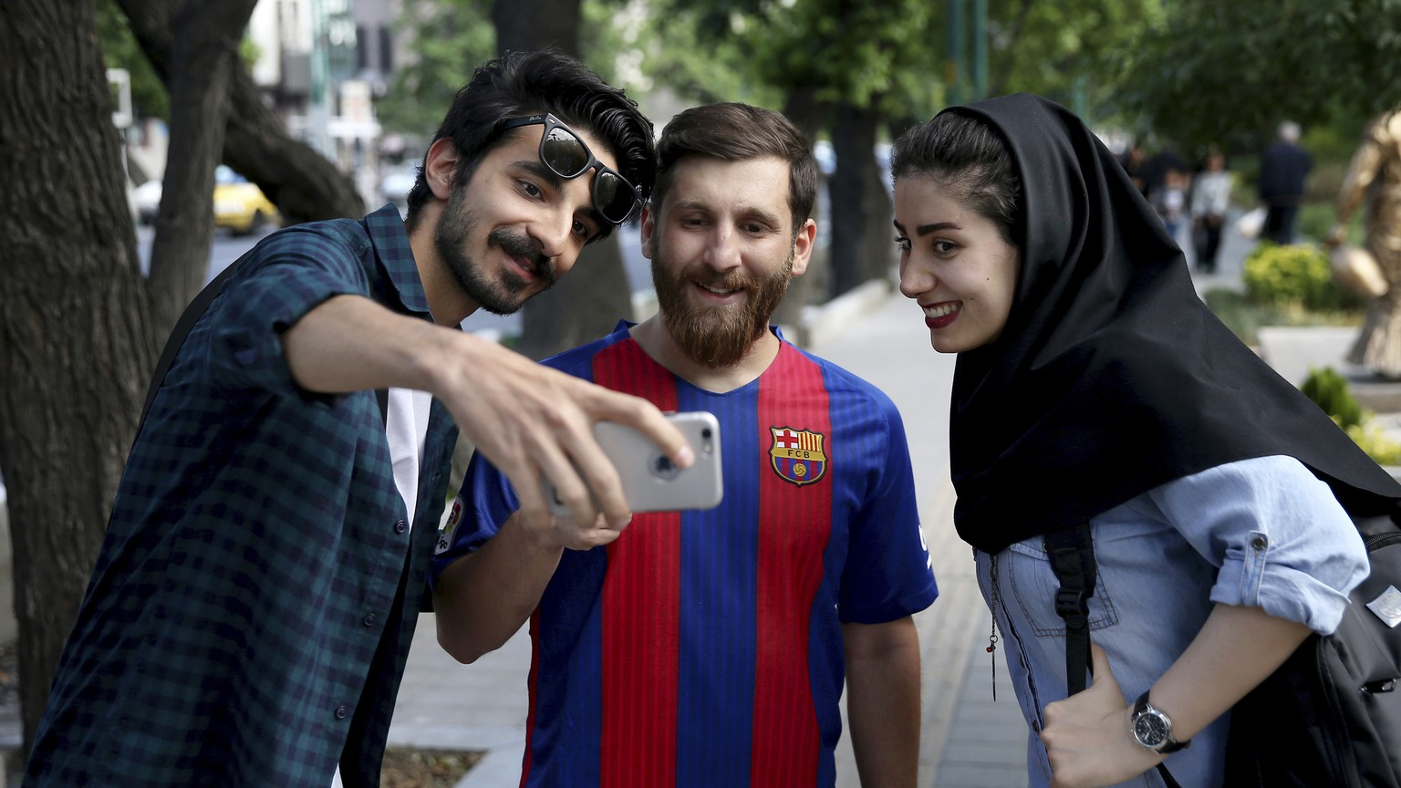 In this Monday, May 8, 2017 photo, two Iranians take a selfie with Reza Parastesh, Iranian doppelganger, or look-alike, of Lionel Messi, Argentinian soccer legend in Tehran, Iran. (AP Photo/Ebrahim Noroozi)