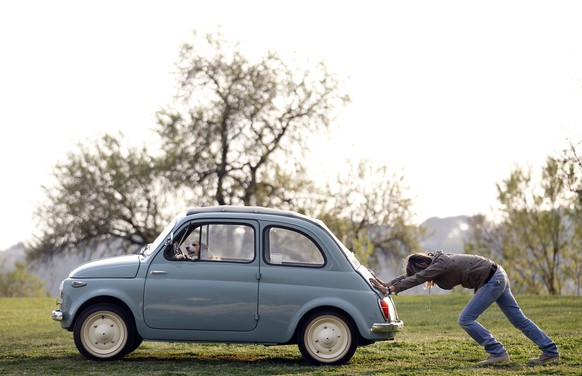A woman pushes her Fiat 500 car as her dog sits inside, in a neighbourhood of Rome in this March 23, 2012 file photo.  To match Special Report EUROPE-DEFLATION/ITALY    REUTERS/Alessandro Bianchi/Files  (ITALY - Tags: ANIMALS TRANSPORT SOCIETY BUSINESS POLITICS)