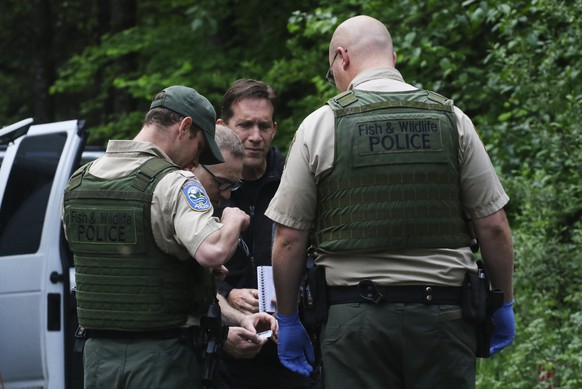 Washington State Fish and Wildlife Police confer with an individual from the King County Medical Examiner's and a King County Sheriff's deputy on a remote gravel road above Snoqualmie, WA., following a fatal cougar attack. Saturday May 19, 2018. One man was killed and another seriously injured when they encountered a cougar Saturday while mountain biking in Washington state, officials said. (Alan Berner /The Seattle Times via AP)