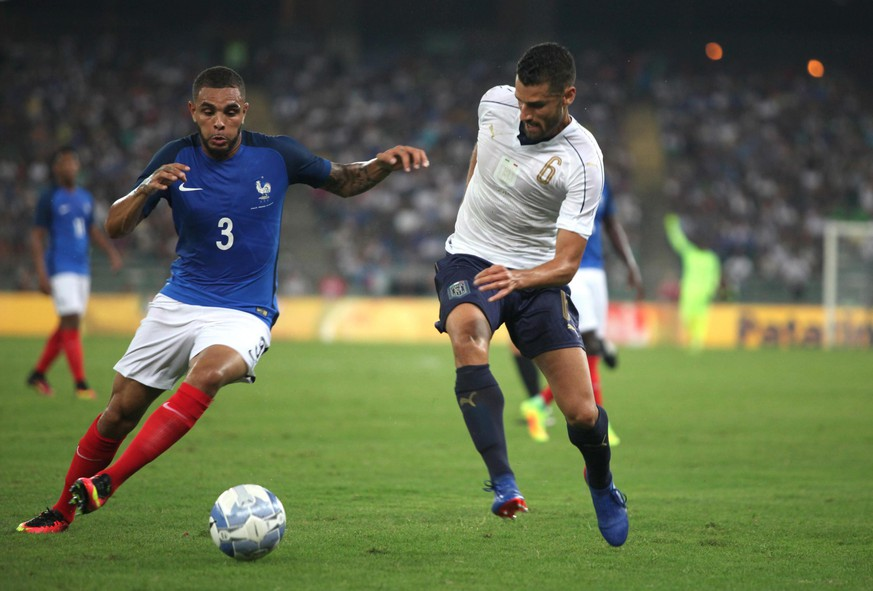 epa05519242 France's Layvin Kurzawa (L) in action  during the international friendly soccer match between Italy and France at San Nicola Stadium in Bari, 01 September 2016.  EPA/TONY VECE