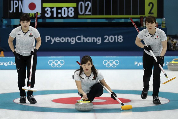 Japan's Chinami Yoshida, center, prepares to throw the stone during their women's curling match against Denmark at the 2018 Winter Olympics in Gangneung, South Korea, Thursday, Feb. 15, 2018. (AP Photo/Aaron Favila)