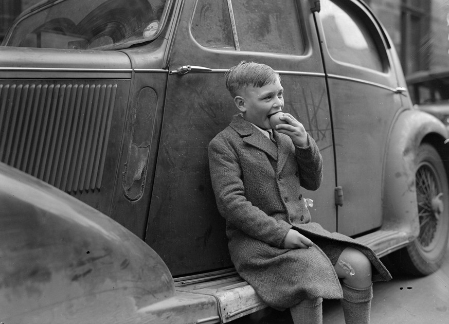 1945:  A boy sits on the running board of a car, eating an apple.  (Photo by Express/Express/Getty Images)