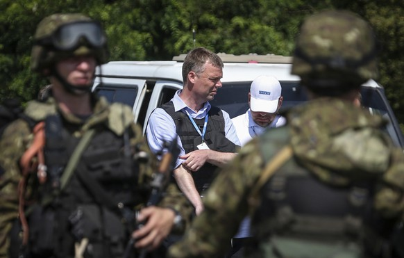 Alexander Hug (C), deputy head for the Organisation for Security and Cooperation in Europe's (OSCE) monitoring mission in Ukraine, looks on next to armed pro-Russian separatists on the way to the site in eastern Ukraine where the downed Malaysia Airlines flight MH17 crashed, outside Donetsk, July 30, 2014. REUTERS/Sergei Karpukhin (UKRAINE - Tags: TRANSPORT CIVIL UNREST DISASTER POLITICS CONFLICT)