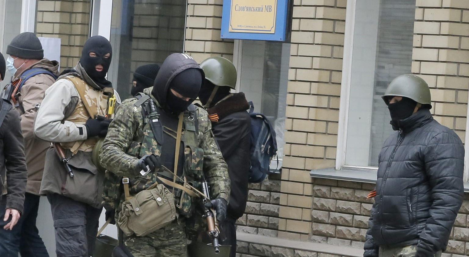 Armed pro-Russian activists occupying the police station in the eastern Ukraine town of Slovyansk carry riot shields on Saturday, April 12, 2014. Pro-Moscow protesters have seized a number of government buildings in the east over the past week, undermining the authority of the interim government in the capital, Kiev. (AP Photo/Efrem Lukatsky)