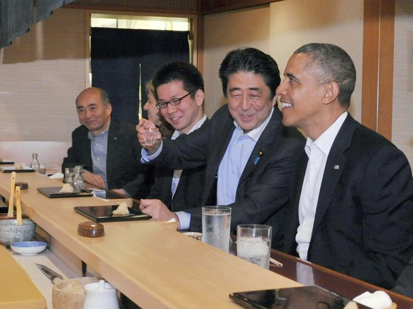In this photo taken Wednesday, April 23, 2014 and released by Japan's Cabinet Public Relations Office, Japanese Prime Minister Shinzo Abe, second right, shares a laugh with U.S. President Barack Obama as they have dinner at Sukiyabashi Jiro sushi restaurant in Tokyo. Obama is on a three-day state visit to Japan. Others are from left, Japanese Ambassador to the United States Kenichiro Sasae, U.S. Ambassador to Japan Caroline Kennedy and an unidentified interpreter. (AP Photo/Cabinet Public Relations Office, Japan Pool) JAPAN OUT