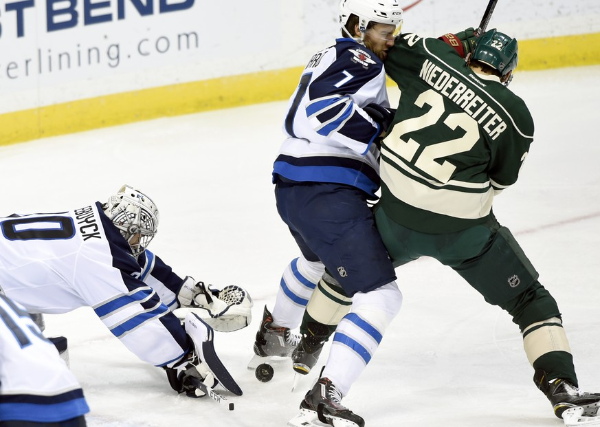 Winnipeg Jets goalie Connor Hellebuyck (30) covers up the puck as defenseman Ben Chiarot (7) pushes Minnesota Wild right wing Nino Niederreiter (22), of Switzerland, away during the third period of an NHL hockey game Friday, Jan. 15, 2016, in St. Paul, Minn. The Jets won 1-0. (AP Photo/Hannah Foslien)