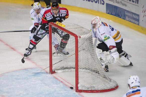 Le joueur fribourgeois Marc-Antoine Pouliot, gauche, marque le 6eme but au gardien biennois Simon Rytz, droite, lors du match du championnat suisse de hockey sur glace de National League A, entre le HC Fribourg-Gotteron et le EHC Biel-Bienne, ce vendredi 31 octobre 2014 a la patinoire de la BCF Arena de Fribourg. (KEYSTONE/Jean-Christophe Bott)
