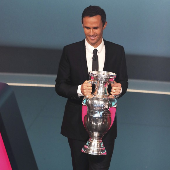 Former Portuguese soccer player and European champion Ricardo Carvalho brings the trophy to the stage during the UEFA Euro 2020 European soccer championship qualifying draw at the Convention Centre in Dublin, Ireland, Sunday, Dec. 2, 2018. (AP Photo/Peter Morrison)