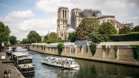 epa07760432 A touristic boat cruises in front of the Notre-Dame Cathedral in Paris, France 07 August 2019. The yard has been stopped since analyzes proving an excessive presence of lead and the risks taken by the workers three months after the Cathedral was badly damaged by a huge fire last 15 April.  EPA/CHRISTOPHE PETIT TESSON