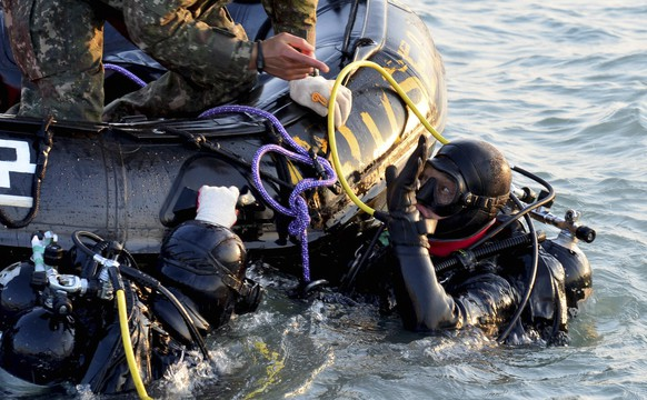 Divers operate at the site where the capsized passenger ship Sewol sank in the sea off Jindo, during the search and rescue operation in the sea off Jindo, April 22, 2014, in this picture provided by South Korean Navy and released by Yonhap on April 23, 2014. South Korean divers swam though dark, cold waters into a sunken ferry on Wednesday, feeling for children's bodies with their hands in a maze of cabins, corridors and upturned decks as they searched for hundreds of missing.The divers, with oxygen and communications lines trailing, can only see a few inches in front of them in the wreckage of the ship that started sinking a week ago after a sharp turn. REUTERS/South Korean Navy/Yonhap (SOUTH KOREA - Tags: DISASTER MARITIME MILITARY)  ATTENTION EDITORS - THIS IMAGE WAS PROVIDED BY A THIRD PARTY. FOR EDITORIAL USE ONLY. NOT FOR SALE FOR MARKETING OR ADVERTISING CAMPAIGNS. THIS PICTURE IS DISTRIBUTED EXACTLY AS RECEIVED BY REUTERS, AS A SERVICE TO CLIENTS. NO SALES. NO ARCHIVES. SOUTH KOREA OUT. NO COMMERCIAL OR EDITORIAL SALES IN SOUTH KOREA
