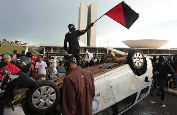epa05652746 Protesters overturn a vehicle outside the Brazilian Congress, during a protest against the fiscal adjustment promoted by the government of President Michel Temer and for maneuvers that may lead to amnesty for those guilty of corruption in Brasilia, Brasil, 29 November 2016. The demonstration was convened by student movements and unions in conjunction with the vote on some measures of that fiscal adjustment in the Senate and a package of new initiatives against corruption in the Chamber of Deputies.  EPA/JOEDSON ALVES