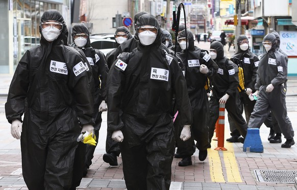 South Korean army soldiers wearing protective suits move to spray disinfectant in Daegu, South Korea, Sunday, March 15, 2020. For most people, the new coronavirus causes only mild or moderate symptoms, such as fever and cough. For some, especially older adults and people with existing health problems, it can cause more severe illness, including pneumonia. (Kim Hyun-tae/Yonhap via AP)