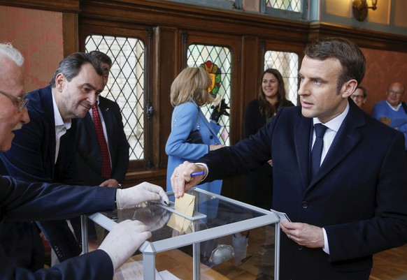 French President Emmanuel Macron casts his ballot for the first round of the mayoral elections in Le Touquet, northern France, Sunday March 15, 2020. France is holding nationwide elections Sunday to choose all of its mayors and other local leaders despite a crackdown on public gatherings because of the new virus. (Pascal Rossignol/Pool via AP)