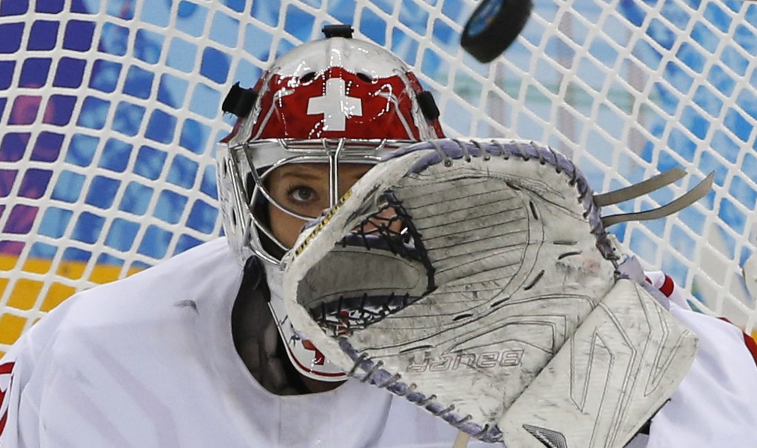 Switzerland's goalie Florence Schelling makes a save against Team USA during the third period of their women's preliminary round hockey game at the Sochi 2014 Winter Olympic Games February 10, 2014. REUTERS/Grigory Dukor (RUSSIA  - Tags: SPORT ICE HOCKEY OLYMPICS TPX IMAGES OF THE DAY)