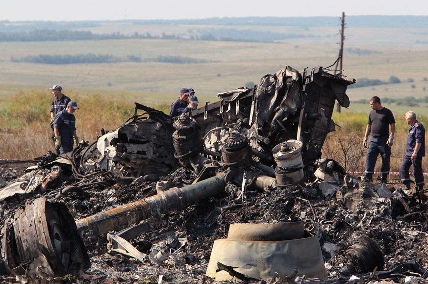 epa06762372 (FILE) - Ukrainian workers inspect debris at the main crash site of the Boeing 777 Malaysia Airlines flight MH17, which crashed over the eastern Ukraine region, near Grabovo, some 100 km east of Donetsk, Ukraine, 20 July 2014 (reissued 25 May 2018). Australia and The Netherlands on 25 May 2018, have formally accused Russia of being responsible for the downing of Malaysia Airlines' Boeing 777 plane flight MH17, en route from Amsterdam to Kuala Lumpur, over eastern Ukraine in July 2014, resulting in the death of 298 people.  EPA/IGOR KOVALENKO *** Local Caption *** 51489738