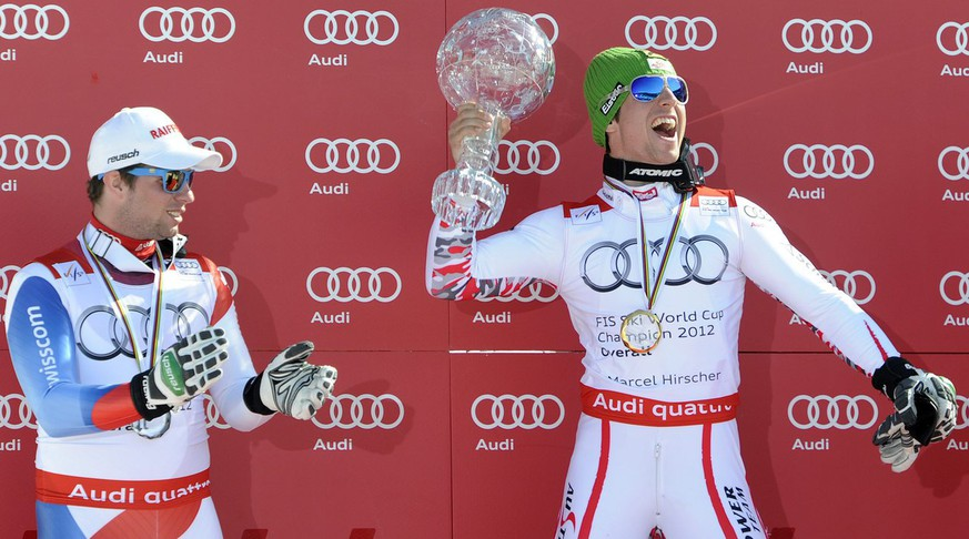 Austrian Marcel Hirscher right, celebrates in the finish area holding the crystal globe of the winner of the Overall standing next to Switzerland's Beat Feuz, left, 2n place of the overall standing at the Alpine Ski World Cup finals, in Schladming, Austria, Sunday, March 18, 2012. (KEYSTONE/Jean-Christophe Bott)