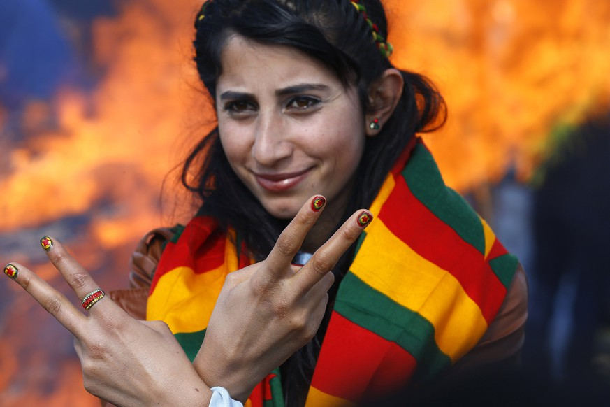 A woman shows off her nails after being painted with the colours of the flag of Kurdistan Workers Party (PKK) during a gathering celebrating Newroz, which marks the arrival of spring and the new year, in the border town of Suruc, Sanliurfa province March 17, 2015. REUTERS/Umit Bektas (TURKEY - Tags: POLITICS CIVIL UNREST ANNIVERSARY)