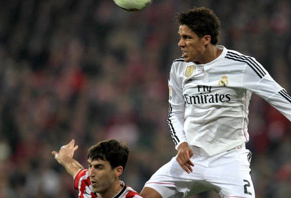 epa04652364 Real Madrid's Raphael Varane (R) in action against Athletic Club Bilbao's Andoni Iraola during the Spanish Liga Primera Division match between Athletic Bilbao and Real Madrid at San Mames stadium in Bilbao, Spain, 07 March 2015.  EPA/LUIS TEJIDO