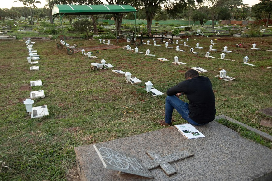 epaselect epa08436515 A man cries for his relative victim of Covid-19 in the Campo de Esperanza cemetery in Brasilia, Brazil, 21 May 2020. Brazil has already registered at least 291,579 cases and around 19,000 coronavirus deaths, although the numbers could be much higher due to high underreporting and the delay in carrying out the tests.  EPA/Joedson Alves