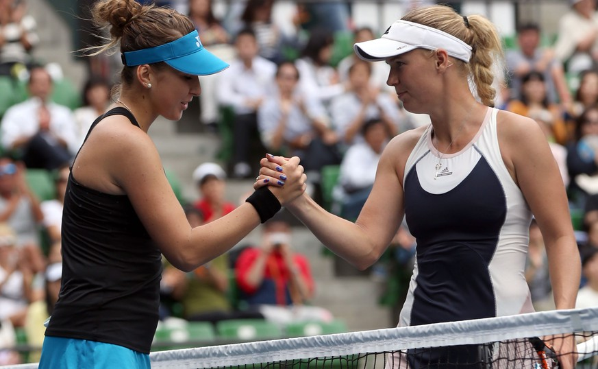 Belinda Bencic, left, of Switzerl and Caroline Wozniacki, right, of Denmark greet each other after their semifinal match at the Pan Pacific Open women's tennis tournament in Tokyo, Saturday, Sept. 26, 2015. (AP Photo/Eugene Hoshiko)