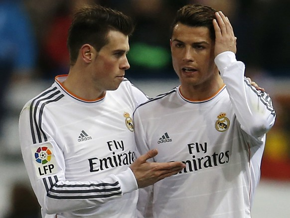Real Madrid's Cristiano Ronaldo (R) listens to his team mate Gareth Bale during their Spanish King's Cup semi-final second leg soccer match against Atletico Madrid at Vicente Calderon stadium in Madrid February 11, 2014.  REUTERS/Sergio Perez  (SPAIN - Tags: SPORT SOCCER)