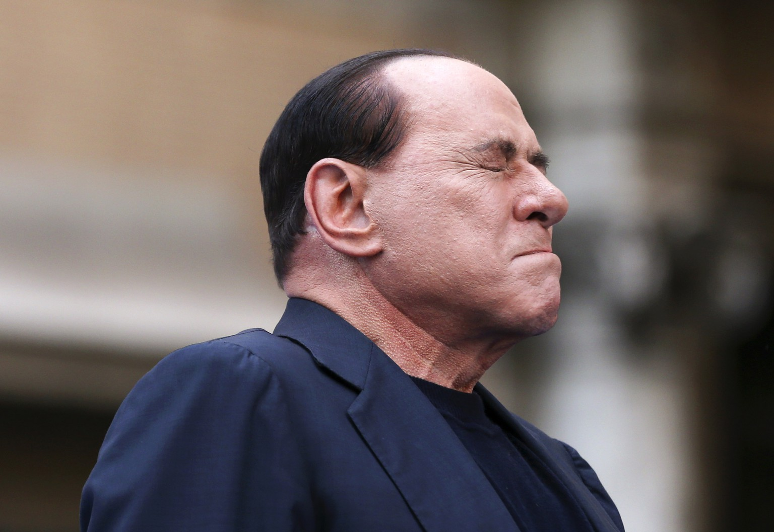 Former Italian Prime Minister Silvio Berlusconi closes his eyes in a gesture to supporters during a rally to protest his tax fraud conviction, outside his palace in central Rome in this August 4, 2013 file photo. Both the prosecution and defence have asked a Milan court to order former Prime Minister Silvio Berlusconi to serve a one-year sentence for tax fraud doing community service, judicial sources said on April 10, 2014. The judge told reporters after the first day of hearings that the court would decide in 5-15 days what kind of punishment the centre-right leader will receive.