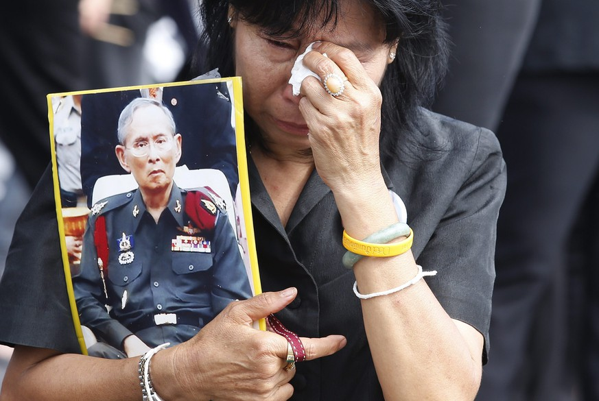 epa05597359 A Thai mourner holds a portrait of late Thai King Bhumibol Adulyadej as she takes part in a mass royal anthem singing to honor the late Thai King Bhumibol Adulyadej at Sanam Luang (Royal Field) opposite the Grand Palace in Bangkok, Thailand, 22 October 2016. Tens of thousands of mourners gathered to sing the Royal Anthem, and event that was filmed for screening on television and at cinemas. The event was organized by MC Chatrichalerm Yukol, who is a national artist and filmmaker. King Bhumibol, the world's longest reigning monarch, died at the age of 88 in Siriraj Hospital in Bangkok on 13 October 2016.  EPA/NARONG SANGNAK