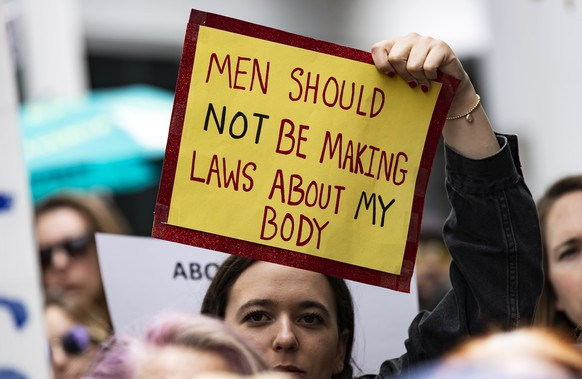 epa07590165 A woman holds a poster reading 'Men Should Not Be Making Laws About My Body' as pro-abortion protesters demonstrate at the West Hollywood City Hall in Hollywood, California, USA, 21 May 2019. Nationwide protests have activists calling for reproductive freedom and a halt to new laws limiting and criminalizing abortion services.  EPA/ETIENNE LAURENT