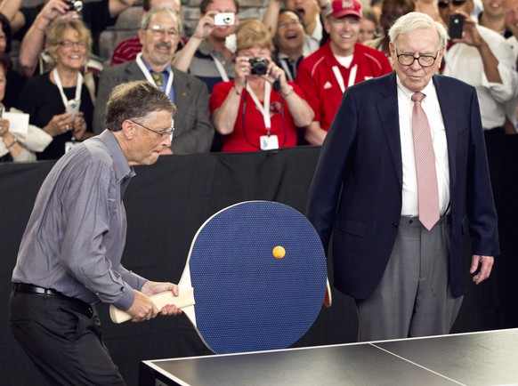 FILE - In this May 6, 2012 file photo, Warren Buffett, chairman and CEO of Berkshire Hathaway, right, watches Bill Gates use an oversize paddle as they play doubles against table tennis prodigy Ariel Hsing in Omaha, Neb. Members of the economic elite are looking for ways to reduce the nation's growing income inequality for a variety of reasons, from self-interest to pangs of conscience. Buffet advocated for a progressive estate tax before members of Congress, saying in 2007,